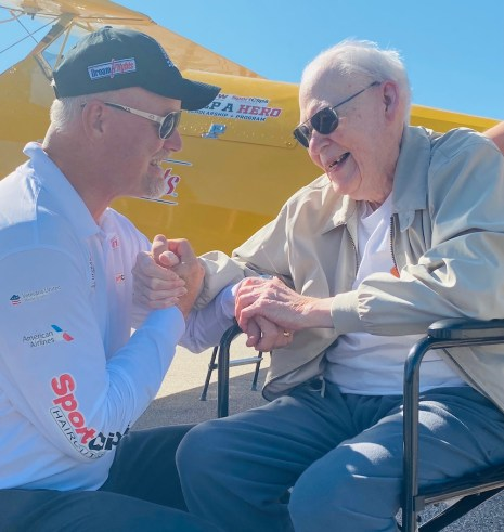 WWII vet thanks clenches hands with his pilot after flight.
