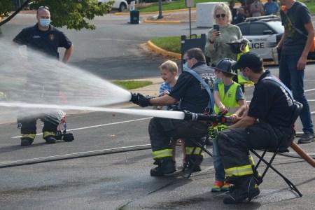 A boy gets a little help holding a fire hose.