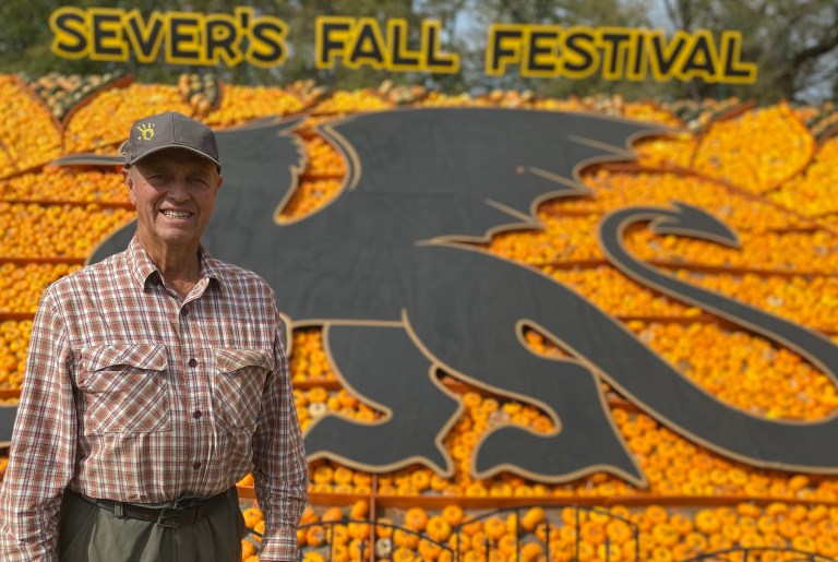 Sever Peterson stands in front of a large dragon cutout surrounded by colorful pumpkins, gourds and squash.