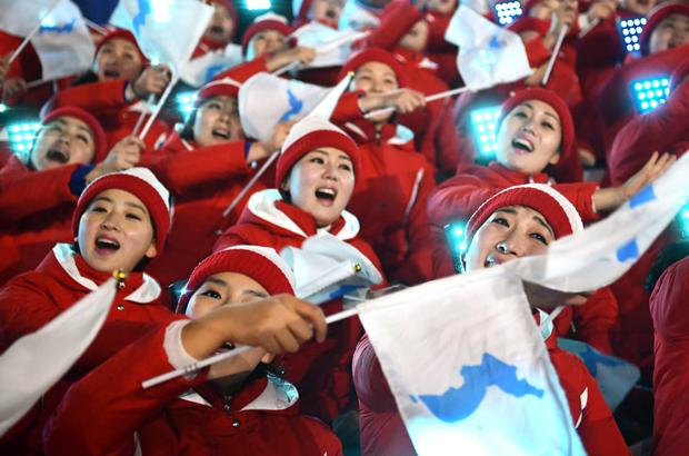 Membras da equipe de torcedoras da Coreia do Norte agitam bandeiras nacionais antes da cerimônia de abertura dos Jogos Olímpicos de Inverno de 2018 no Estádio Pyeongchang, na Coreia do Sul, em 9 de fevereiro de 2018 (Franck Fife/AFP/Getty Images)