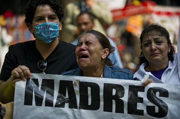 Mãe chora durante protesto na Cidade do México em 10 de maio de 2013. Um grupo de mães e parentes de crianças desapareidas devido à guerra contra as drogas no país exigem que o governo investigue os crimes (Ronaldo Schemidt/AFP/Getty Images)