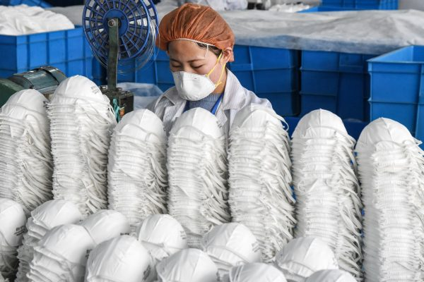 Uma trabalhadora que produz máscaras faciais em uma fábrica na cidade de Handan, província de Hebei, China, em 28 de fevereiro de 2020 (Str / AFP via Getty Images)