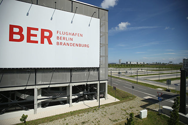 SCHOENEFELD, GERMANY - JUNE 02: A billboard hangs on th side of a parking garage next to an empty parking lot at the unfinished new BER Willy Brandt Berlin Brandenburg International Airport on June 2, 2014 in Schoenefeld, Germany. The airport, which is years behind schedule with no opening date yet in sight, has now been hit by a corruption scandal involving head technician Jochen Grossmann, who is accused of demanding a EUR 500,000 bribe from a contracting firm. The airport's governing body is meeting today and has designated a task force to determine whether Grossmnn might have demanded bribes from other companies as well. (Photo by Sean Gallup/Getty Images)