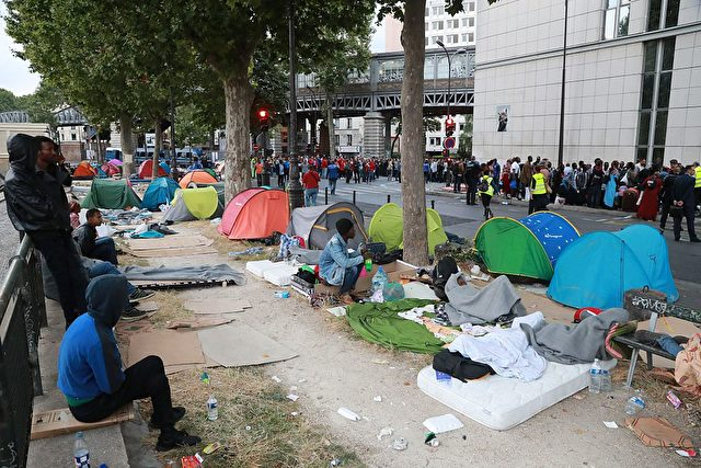 Migrants wait during the evacuation from a makeshift camp by French gendarmes, on July 22, 2016 in Paris. Between 1,200 and 1,400 people, mostly men, from Eritrea, Somalia and Afghanistan, were in this camp near the metro stations Jaures and Colonel Fabien. / AFP / JACQUES DEMARTHON        (Photo credit should read JACQUES DEMARTHON/AFP/Getty Images)