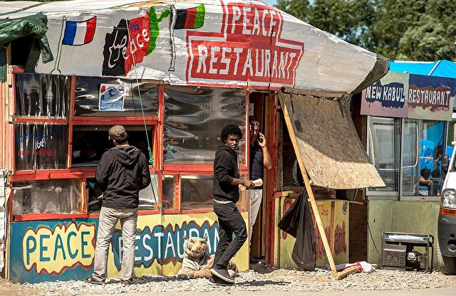"""Migrants walk in front of makeshift restaurants in the so-called 'Jungle' migrant camp in the French northern port city of Calais on August 12, 2016. A French judge on Friday rejected a bid by authorities in Calais to close unlicensed shops and eateries in the migrant camp. The authorities sought an emergency order to close 72 unlicensed stalls and restaurants dotted among the tents housing at least 4,500 migrants and asylum-seekers who are aiming to reach Britain. But in his ruling, the judge said that while the concerns expressed were """"completely understandable,"""" the matter was not urgent enough to warrant the expulsion of the vendors. / AFP / PHILIPPE HUGUEN (Photo credit should read PHILIPPE HUGUEN/AFP/Getty Images)"""