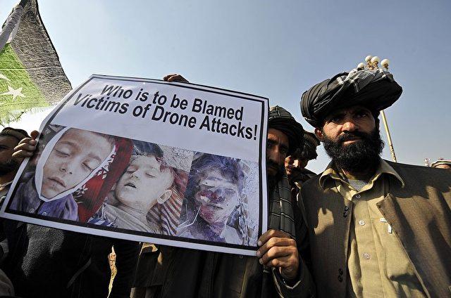 """Pakistanische Männer protestieren gegen Drohnen-Angriffe und fragen """"Wer sind die Schuldigen - Opfer der Drohnen-Angriffe"""" Foto: AAMIR QURESHI/Getty Images"""