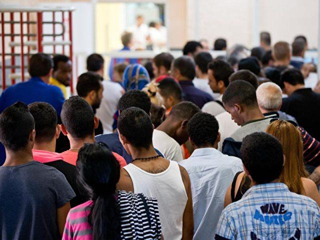 Asylbewerber stehen im bayrischen Zirndorf Am Eingang zur Kantine in einer Zentralen Aufnahmeeinrichtung für Asylbewerberunterkunft. Viele Deutsche sind einer Umfrage zufolge der Auffassung, Kanzlerin Merkel müsse ihre Flüchtlingspolitik grundsätzlich ändern. Foto: Daniel Karmann/Archiv/dpa