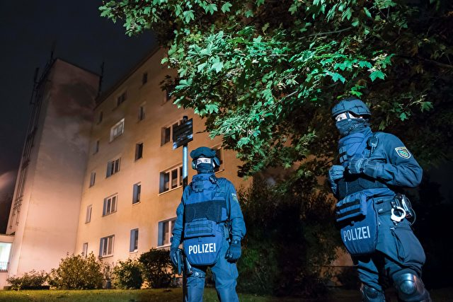 """Policemen in protective cllothing stand in front of at a residential building in Chemnitz, eastern Germany, on October 8, 2016. Police found several hundred grams of """"explosive materials"""" in the east German apartment of a Syrian man suspected of planning a bomb attack, and arrested three people connected to him. The suspect who remains at large, 22-year-old Syrian Jaber Albakr, could have had """"an Islamist motive"""" sources close to the police told AFP.  / AFP / Jens-Ulrich Koch        (Photo credit should read JENS-ULRICH KOCH/AFP/Getty Images)"""