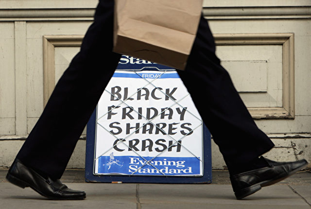 LONDON - OCTOBER 10:  A city worker passes the Evening Standard headline board showing the words 'Black Friday Shares Crash' during lunch time on Friday on October 10, 2008 in London, England. Shares worldwide  have fallen dramatically as fears grow of a widespread recession.  (Photo by Cate Gillon/Getty Images)