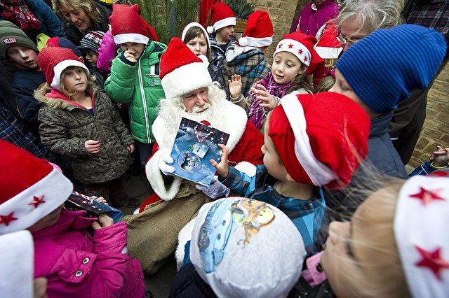 Ein Mann als Weihnachtsmann verkleidet teilt Geschenke an Kinder aus. (Symbolbild) Foto: JOHN MACDOUGALL/AFP/Getty Images