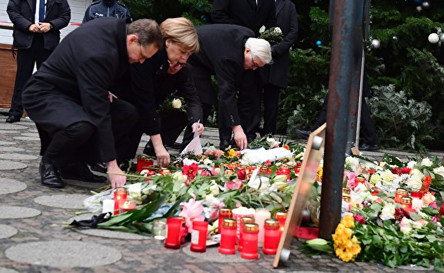 (L-R) Berlin's mayor Michael Mueller, German Chancellor Angela Merkel, German Interior Minister Thomas de Maiziere and German Foreign Minister Frank-Walter Steinmeier lay down flowers at a makeshift memorial for the victims of an attack on December 20, 2016 in front of the Kaiser-Wilhelm-Gedaechtniskirche (Kaiser Wilhelm Memorial Church) in Berlin, where a truck crashed into a Christmas market. Twelve people were killed and almost 50 wounded, 18 seriously, when the lorry tore through the crowd on December 19, 2016, smashing wooden stalls and crushing victims, in scenes reminiscent of July's deadly attack in the French Riviera city of Nice. / AFP / Tobias SCHWARZ (Photo credit should read TOBIAS SCHWARZ/AFP/Getty Images)