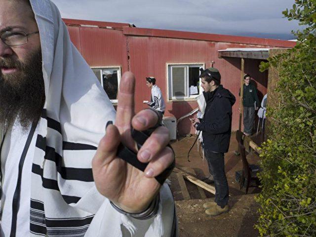 Israelische Siedler nach dem Morgengebet in der umstrittenen Siedlung Amona. Foto: Jim Hollander/dpa