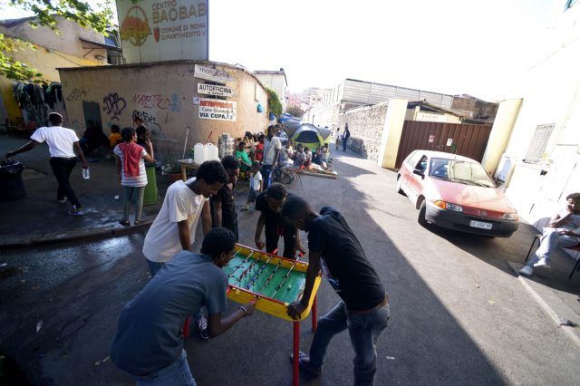 Young migrants play baby-foot in the street of Via Cupa just outside the former Baobab migrants reception centre next to the Tiburtina train station in Rome on August 8, 2016.  Set up almost three years ago the Baobab centre was shut down by police in December 2015 in the wake of Paris attacks. But Baobab volunteers quickly set up a camp on the street in front of the old shelter with tents and chemical toilets, serving three meals a day.  / AFP / FILIPPO MONTEFORTE        (Photo credit should read FILIPPO MONTEFORTE/AFP/Getty Images)