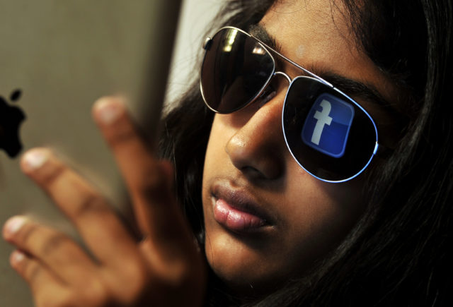 The 'Facebook' logo is reflected in a young Indian woman's sunglasses as she browses on a tablet in Bangalore on May 15, 2012. World's popular and leading social networking company Facebook Inc., founded in a Harvard dorm room by Mark Zuckerberg whose current value exceeds 100 billion USD, will be making an initial public offering (IPO) which is slated to be Silicon Valley's biggest-ever. AFP PHOTO/Manjunath KIRAN (Photo credit should read Manjunath Kiran/AFP/GettyImages)