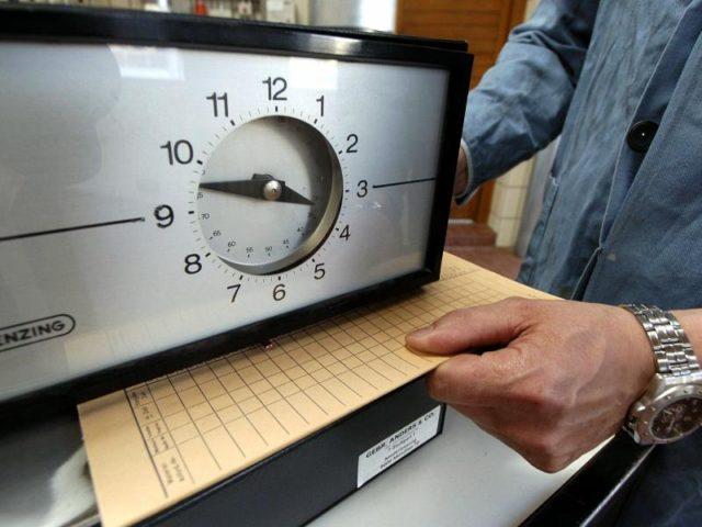 Eine Karte zur Arbeitszeiterfassung wird unter eine Stechuhr gelegt. Foto: Armin Weigel/Symbolbild/dpa