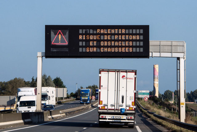 "This picture taken on October 13, 2016 shows a truck driving under a board reading ""Slow down, possible pedestrians and obstacles on the road"", on the circular road next to the ""Jungle"" migrant camp in Calais, northen France. French authorities prepare to raze the Calais ""Jungle"" camp and move thousands of migrants to shelters nationwide. Two towns a few kilometres apart in the countryside near Paris reveal a nation torn between fear and fraternity. / AFP / DENIS CHARLET        (Photo credit should read DENIS CHARLET/AFP/Getty Images)"