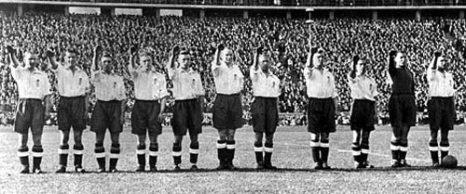 Фотография, сделанная 14 мая 1938 года на олимпийском стадионе Берлина, когда футбольная сборная Британии – принужденная к этому тайным надзором со стороны британского МИДа и Футбольной ассоциации - вскинула руки в нацистском приветствии перед дружеским матчем с Германией. Фото предоставлено автором