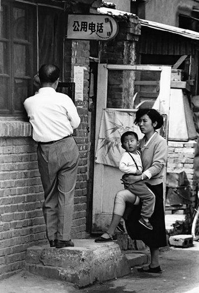 Женщина с ребёнком ждёт своей очереди возле общественного телефона. Фото: Великая Эпоха.