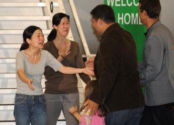 Освобоженные американские журналистки Эуна Ли (слева) обнимает своего мужа Мишэль Салдэйта (второй справа) и дочь Ханну и вторая журналистка Лаура Лин (вторая слева) обнимает своего мужа Иэйн Клэйтона, после освободдения из Северной Кореи, в аэропорте Бурбанк, Калифорния. Фото: ROBYN BECK /AFP /Getty Images