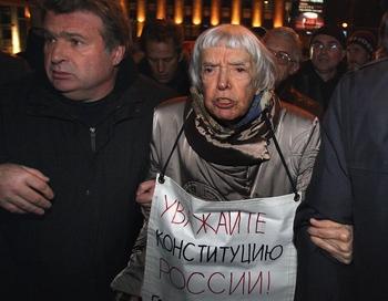 Российская активистка за права человека Людмила Алексеева держит плакат, на котором написано