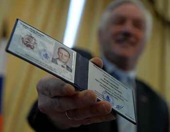 Валентин Горбунов, председатель избирательной комиссии Москвы показывает свидетельство о регистрации Алексея Навального. Фото: KIRILL KUDRYAVTSEV/AFP/Getty Images