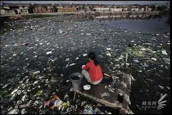 Жительница посёлка Гуйюй провинции Гуандун стирает одежду в местном пруду, сильно загрязнённом промышленными отходами. 25 ноября 2005 год. Фото: Лу Гуан