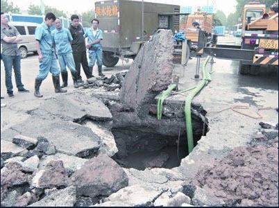 Обвалился участок дороги в городе Ухане провинции Хубэй. В результате были повреждены трубы водопровода, более 1200 жителей района остались без воды. 28 мая 2010 год. Фото с aboluowang.com