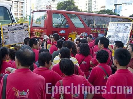 Туристы с коммунистического материка знакомятся с содержанием плакатов последователей Фалуньгун. Фото: The Epoch Times