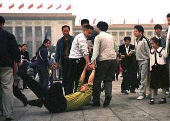 Полицейские агенты арестовывают последователя Фалуньгун, приехавшего в Пекин, чтобы обратиться к правительству. Фото с epochtimes.com