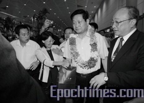 Коммунистический чиновник Ван Цзоань (с венком на шее) поспешно идёт к автомобилю, не обращая внимания на женщину, протягивающую ему в пакете документы обвинения в геноциде. Фото: The Epoch Times