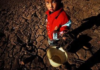 В Китае разразилась сильная засуха. На фото мальчик стоит на засохшем поле в районе города Кунмин провинции Юньнань. 2 февраля 2010 года. Фото: STR/AFP/Getty Images