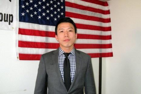 Кенни Ху стоит перед американским флагом. Он сейчас не работает, посвящая всё время спасению отца. Фото: Jenny Liu/The Epoch Times