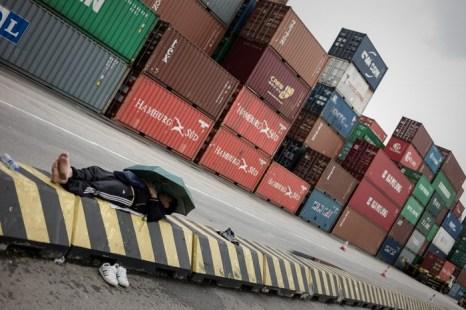 Докер отдыхает у контейнеров терминала Квай Чун, Гонконг, 29 марта 2013 года. Фото: Philippe Lopez/AFP/Getty Images