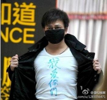 Ли Чэнпэн на презентации своей книги в провинции Сычуань. Он закрыл рот маской, показывая, что ему запретили говорить, и написал на футболке: «Я люблю вас всех». Фото с сайта weibo.com