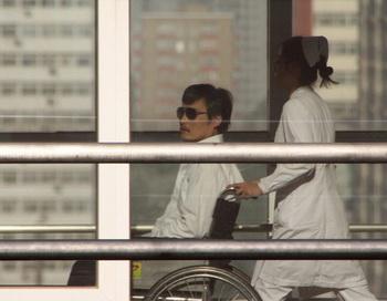 Медсестра перевозит  в инвалидном кресле китайского активиста Чэнь Гуанчэна  в больнице Чаоян в Пекине 2 мая 2012 г. Он согласился оставить  попечение американцев  после получения обещаний безопасности со стороны китайского режима. Фото: Jordan Pouille/AFP/GettyImages