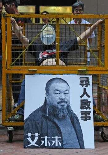 Человек сидит в «тюрьме» в оживленном районе Гонконга, выражая протест против задержания Ай Вэйвэя, 22 апреля 2011 года. Фото: Mike Clarke /AFP /Getty Images