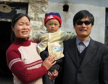 Слепой активист Чэнь Гуанчэн с женой и сыном Чэнь Кэжуем около своего дома в деревне Дуншигу на северо-востоке Китая в провинции Шаньдун, 28 марта 2005 года. Согласно данным американского Госдепартамента, Чэнь с семьёй может свободно выехать в США. Фото: STR/AFP/Getty Images