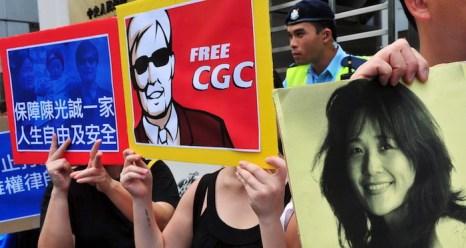 Активисты держат плакаты в поддержку слепого китайского правозащитника Чэнь Гуанчэна и борца за права человека Хэ Пэйжун, которая помогла Чэню 22 апреля сбежать из-под домашнего ареста в деревне Дуншигу. Гонконг, 4 мая. Фото: Laurent Fievet/AFP/GettyImages