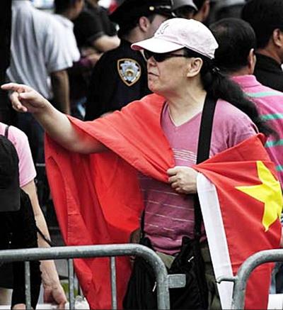 Ли Хуахун, обёрнутая во флаг компартии, 31 мая 2008 года, Флашинг. Ли занималась коммунистической пропагандой в китайском районе Флашинга. Фото: The Epoch Times