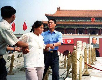 Полицейские арестовывают последовательницу Фалуньгун. Пекин. Фото: minghui.org