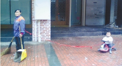Во время уборки улиц мама привязывает к себе сына, чтобы тот не потерялся. Ноябрь 2011 год. Фото с epochtimes.com