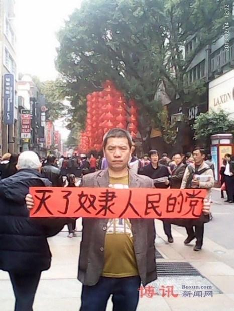 Лю Хуэй держит плакат с надписью: «Уничтожим партию, превратившую народ в рабов!» Февраль 2013 года. Фото с epochtimes.com