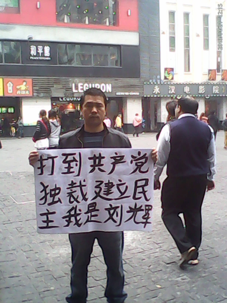 Лю Хуэй держит плакат с надписью: «Долой компартию. Создадим демократию. Меня зовут Лю Хуэй». Февраль 2013 года. Фото с epochtimes.com