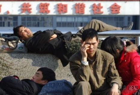 Обрывок надписи сзади гласит «Вместе построим гармоничное общество». Китайцы массово едут домой встречать Новый год. 2013 год. Фото с epochtimes.com