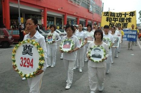 Последователи Фалуньгун несут портреты своих единомышленников, погибших в Китае в результате репрессий со стороны компартии. Малайзия. Фото: The Epoch Times