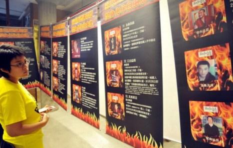 Женщина на выставке рассматривает портреты жертв самосожжения в Тибете, июль, Тайбэй. Китайские коммунистические власти планируют наказывать любого тибетца, призывающего к самосожжению. Фото: Mandy Cheng/AFP/Getty Images