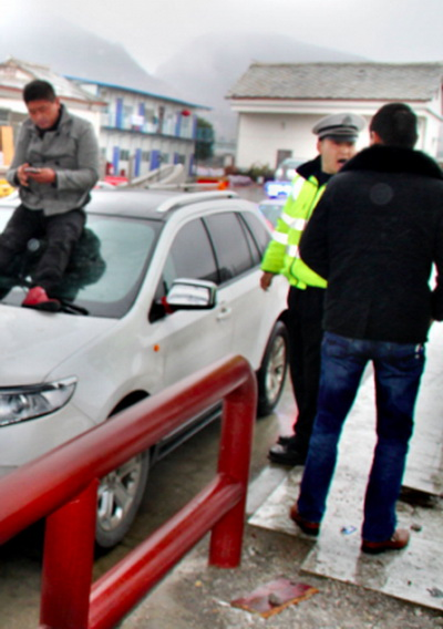 Водитель спорит с полицейским, а Чэнь играет со смартфоном. Фото: Screenshot/ifeng.com