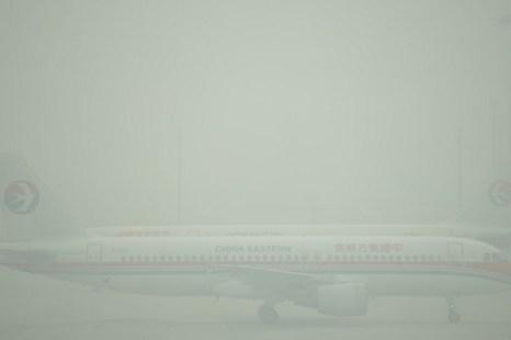 Самолёт едва виден в густом смоге на взлётной полосе аэропорта Хунцяо в Шанхае, 6 декабря 2013 года. Фото: Peter Parks/AFP/Getty Images