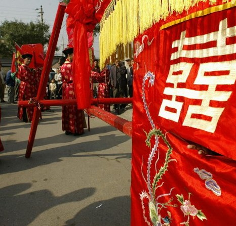 Молодая девушка выглядывает из свадебной кареты во время репетиции традиционной китайской свадьбы в Пекине, 5 октября 2004 года. Фото: Peter Parks/AFP/Getty Images