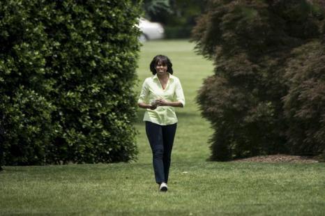 Мишель Обама идёт на встречу с школьниками для сбора урожая в Белом доме. Фото: BRENDAN SMIALOWSKI/AFP/Getty Images